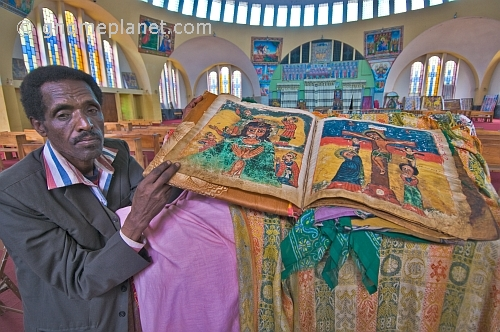 caption: Church warden holds an illustrated vellum Bible in the new church of 'St Mary of Zion'.