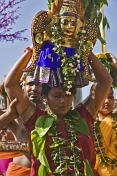 Woman with skewer through her mouth carries statue of Lord Murugan