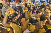 Pilgrims in holy yellow outfits carry pots of milk on their heads