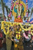 Thaipusam pilgrim with statue of Lord Murugan decorated with flowers