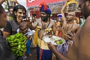 Thaipusam pilgrim anoints baby with sacred ash