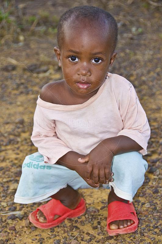 Young Gabonese girl with short hair in a light pink shirt and red shoes.