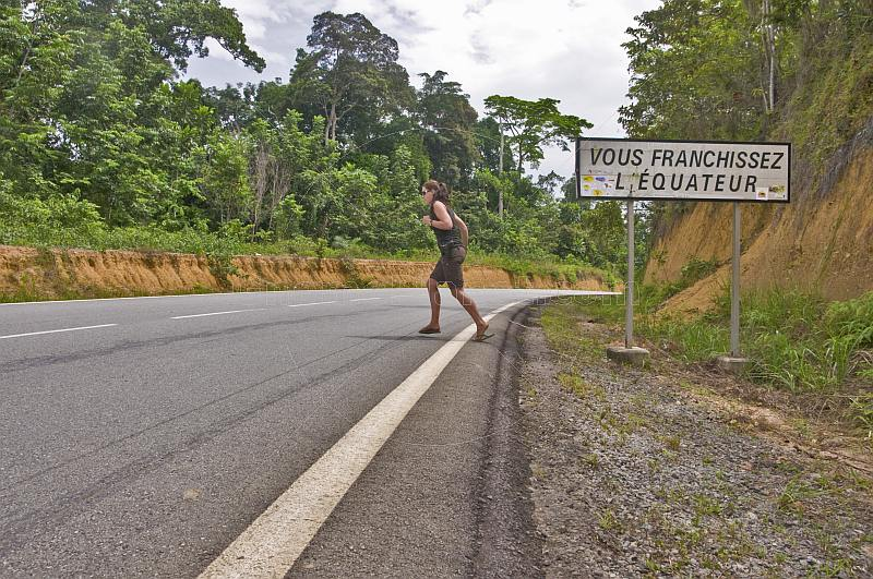 Western woman wearing shorts crosses the Equator on an open road.