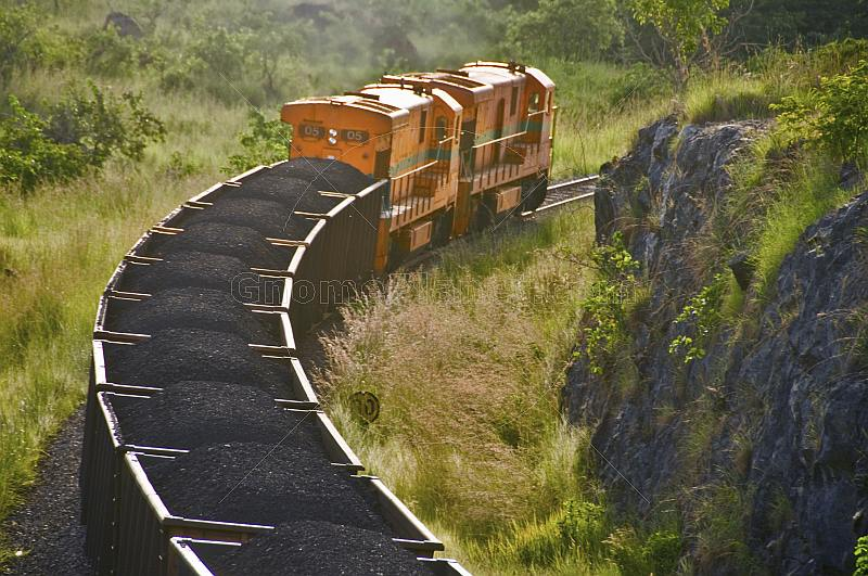 Two diesel locomotives pull a heavily laden coal train through Lope National Park.