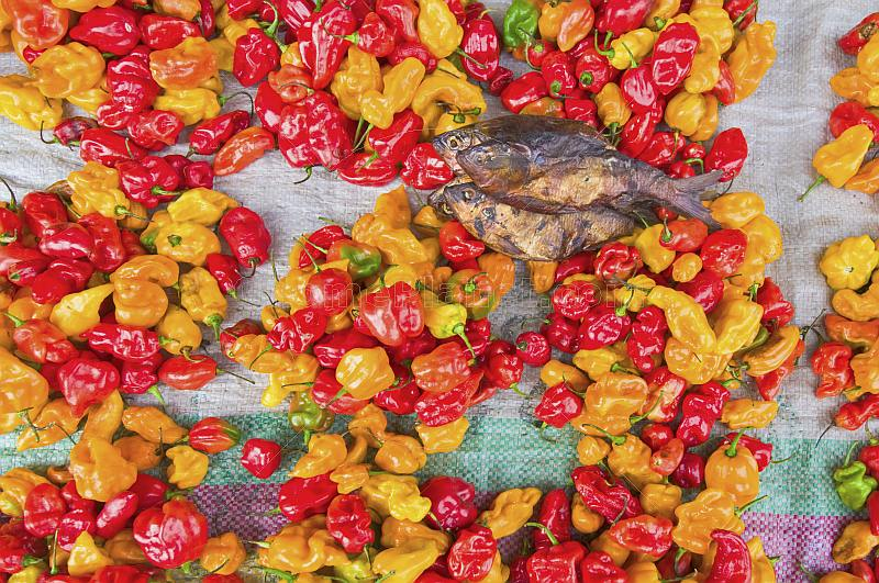 Dried river fish with yellow and red chili peppers on a market stall.