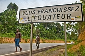 Two Gabonese men walk past the road sign marking the Crossing of the Equator.