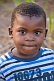 Young Gabonese boy in a white and blue striped sweat shirt.