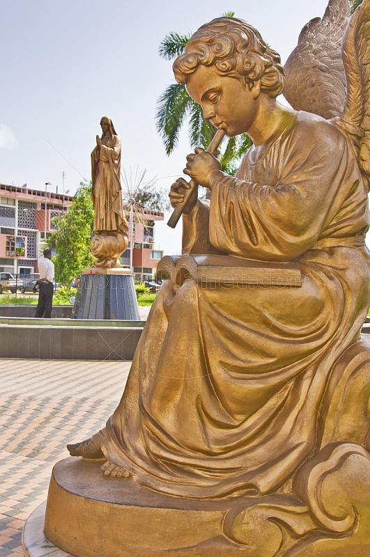 Golden statue of angel playing music in front man praying to the Holy Virgin Mary.