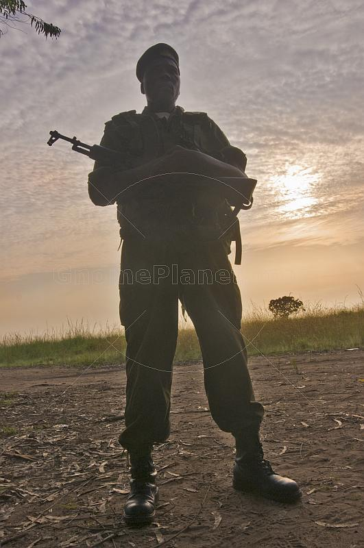 An Angolan soldier with assault rifle silhouetted at dawn.