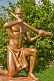 Bronze painted statue of man in loincloth holding a tusk of ivory.