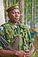 An Angolan soldier with assault rifle in eucalyptus plantation.