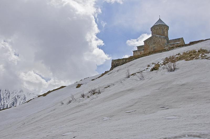 Snow-covered mountains contrast the bare stone of the Tsminda Sameba Monastery.
