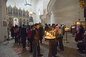 Eastern Orthodox worshippers gather for mass at the Ananuri Monastery, whilst a young mother shows the candlelight to her baby.
