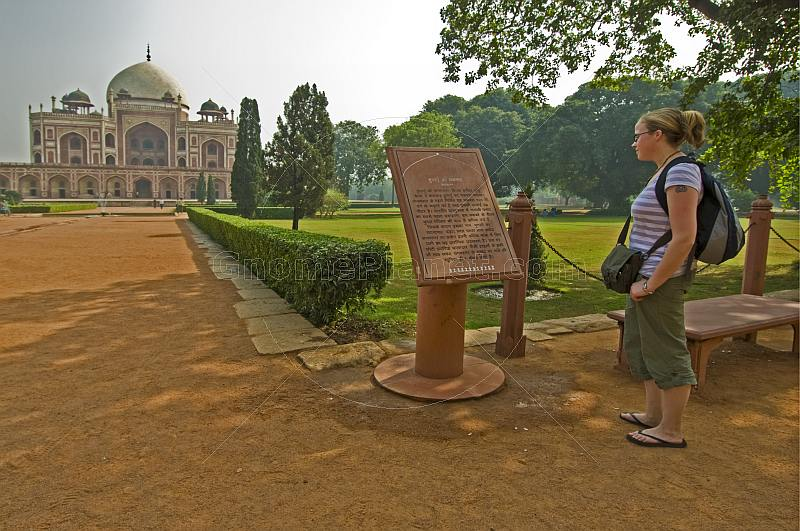 Young female Western tourist reads an account of the history of Humayun's Tomb.