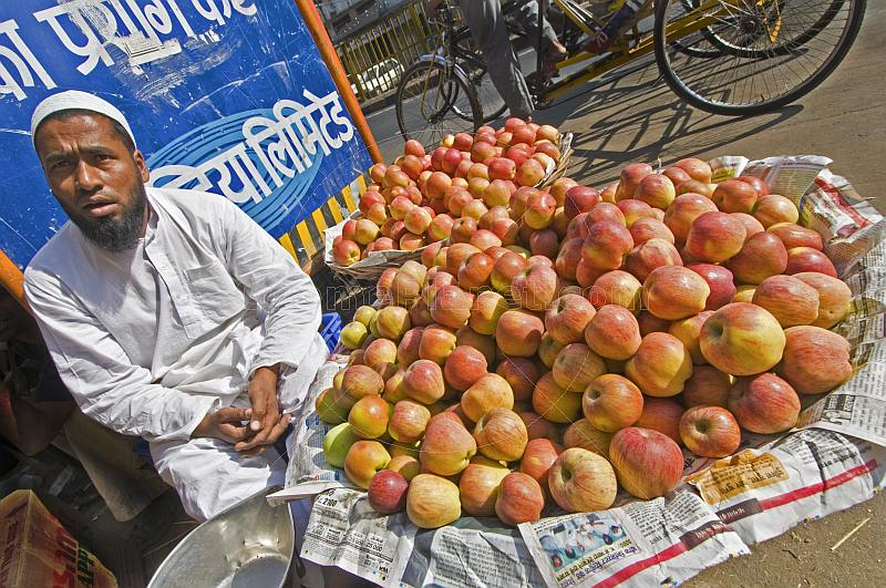 Muslim fruit-seller selling apples on the pavement.