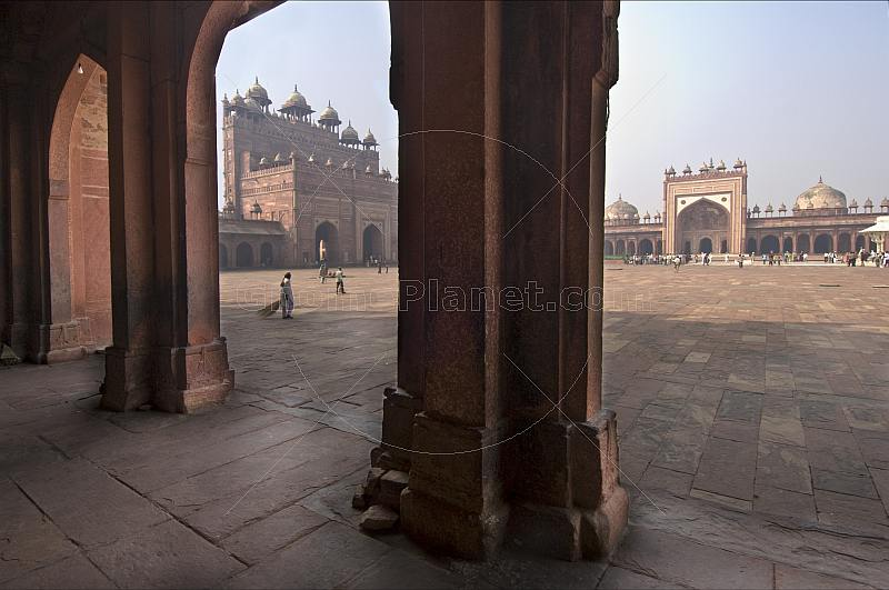 Walkway and courtyard of Akbar's Jami Masjid in early morning light.