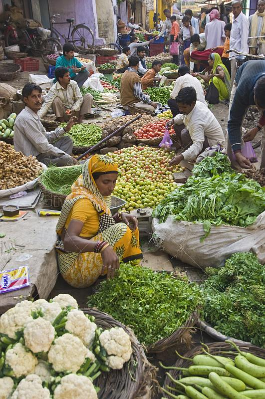 Traders at a busy vegetable markets squat to sell fruit, vegetables, herbs, and fresh spices.