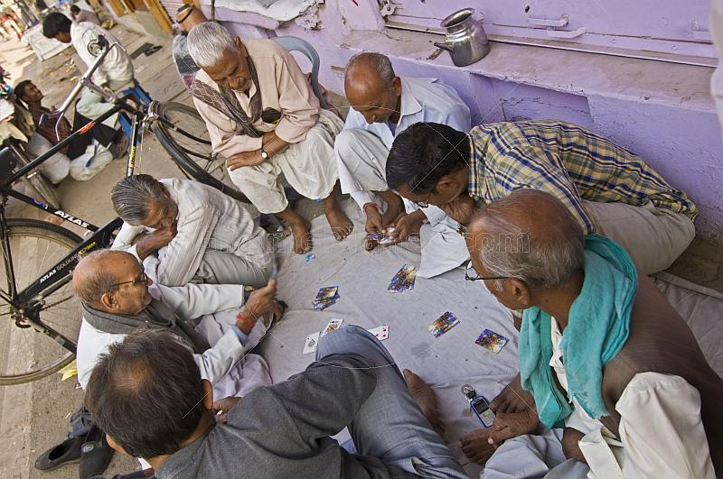 Old men play cards on a sheet spread on the sidewalk.