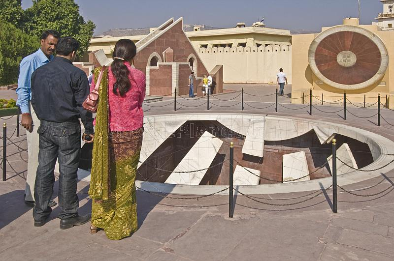 A guide explains details of one of the astronomical instruments at the Jantar Mantar Observatory to an Indian couple.