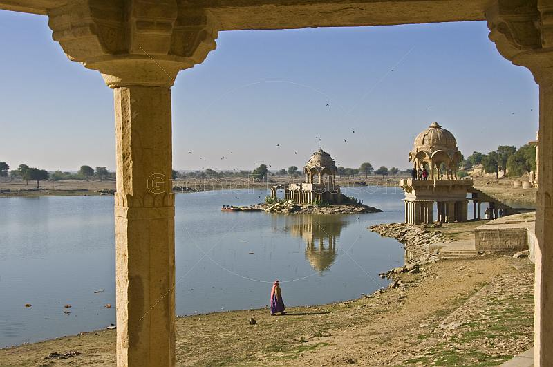 An elderly Indian woman walks along the edge of the Gadi Sagar built 1367 by Maharaja Gadsi Singh.