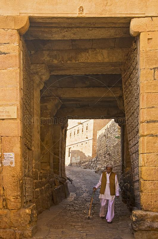 An old man with a walking stick passes through one of the entrance gates to the fort.