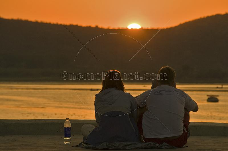 Two western tourists watch the sunset over Lake Pichola.