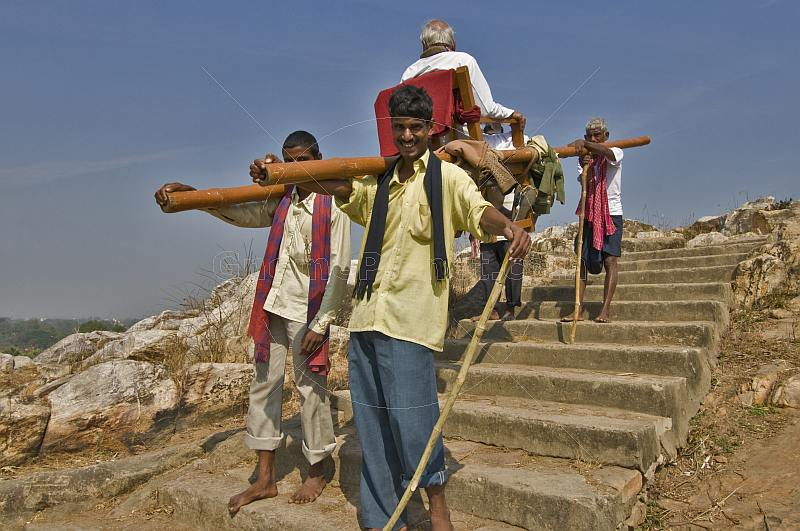 4 Dhooli carriers transport an old man down from the Vaibhara pilgrimage hill.