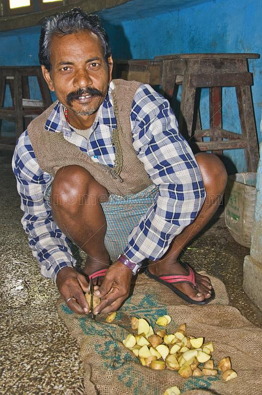 Man cuts and prepares potatoes for a restaurant lunch.