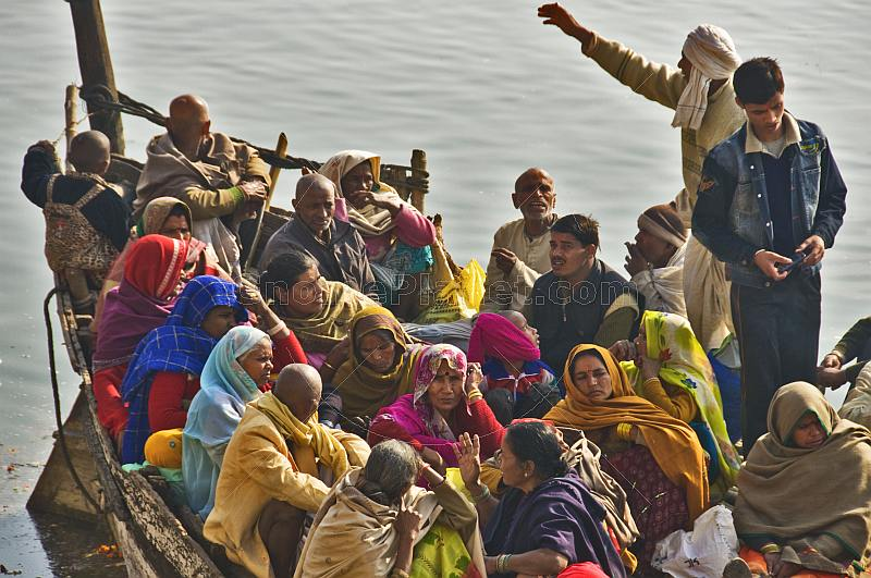 Pilgrims crowd on to a boat to cross the Ganges River.