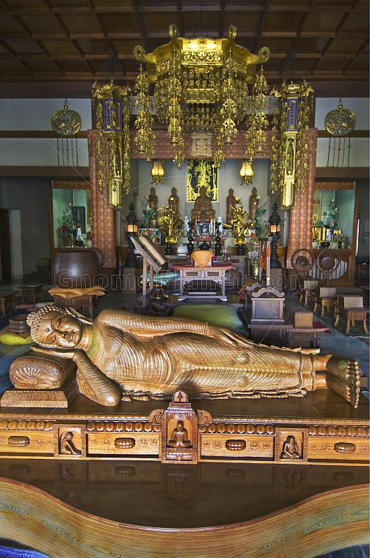 Wooden reclining Buddha statue in front of the altar of the Japanese Temple in Sarnath.