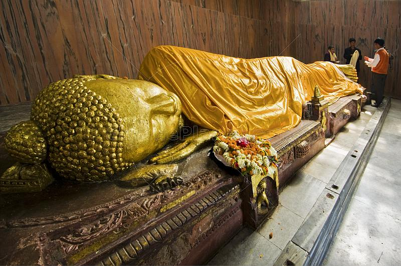 Pilgrims place scarves on the 6m recumbent statue of the dying Buddha in the Parinivarna Temple.