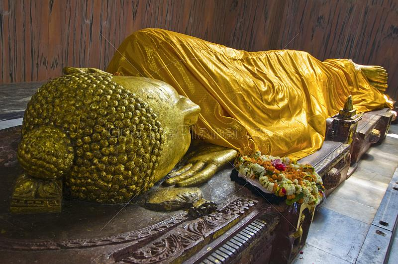 A floral wreath is placed next to the 6m recumbent statue of the dying Buddha in the Parinivarna Temple.