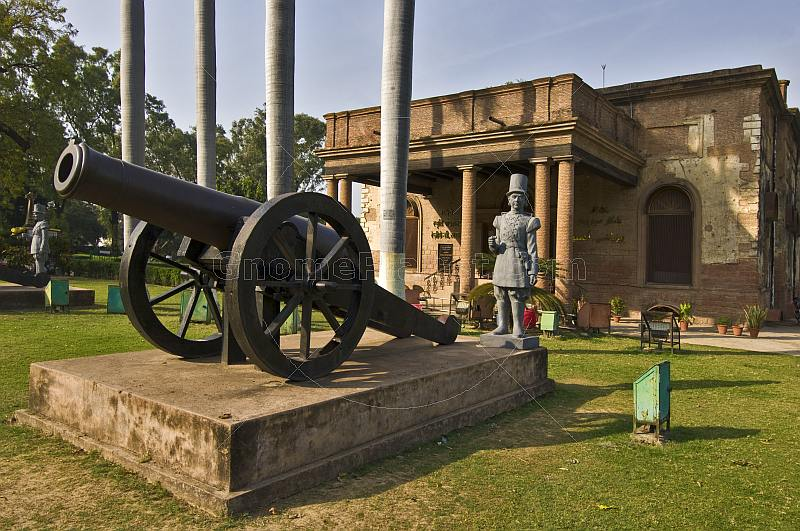 A siege cannon with statue of a period-costumer gunner stand outside the Residency building, now a museum to the Indian Mutiny of 1857.