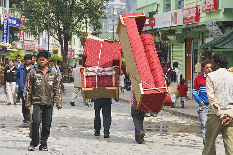 Porters carry a three-piece suite of furniture along the pedestrianised M.G. Marg.