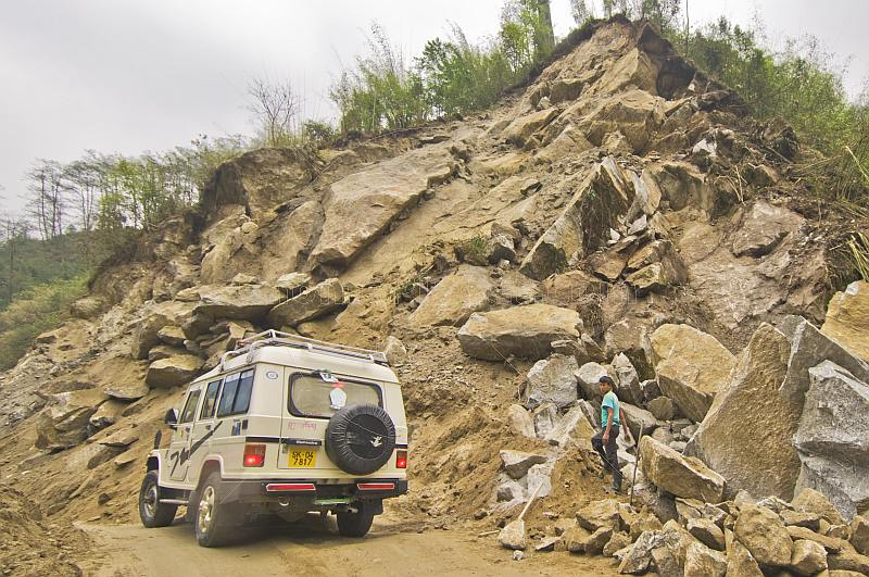 A Mahindra 4wd SUV creeps with care past a dangerous landslide on the road north of Gangtok.