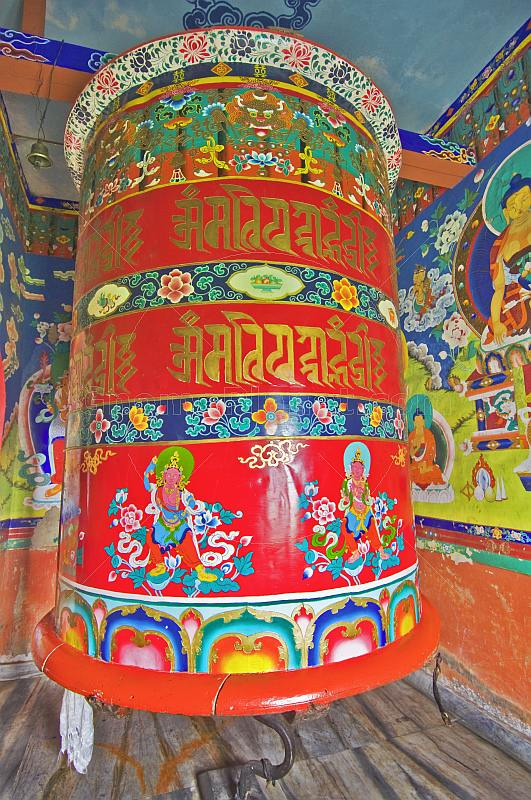 Large colorful prayer wheel in Buddhist monastery.