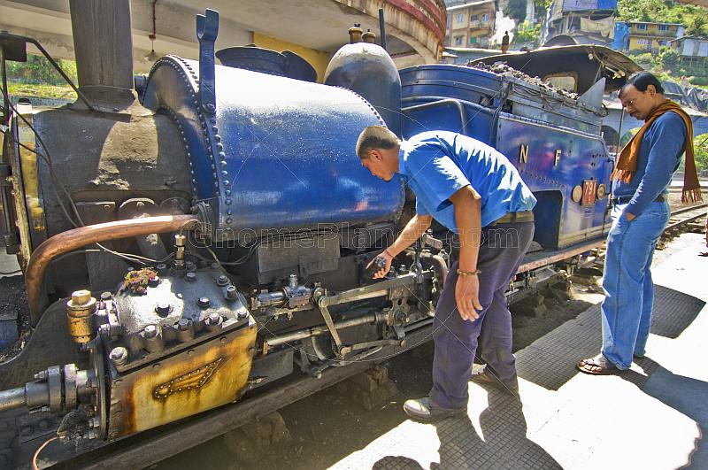 A passenger watches the engineer make adjustments to a steam locomotive on the Darjeeling Himalayan Railway.