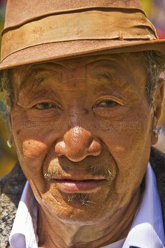 Elderly Buddhist man in hat and earing.