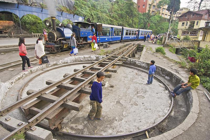 Three boys play on the narrow gauge turntable as a steam train on the Himalayan Mountain Railway approaches Darjeeling Station.