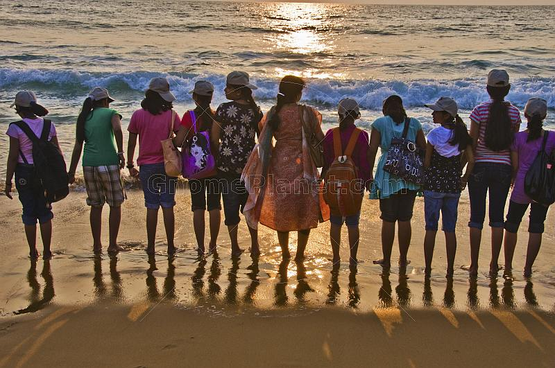 Indian schoolgirls and their teacher line up at the shore to watch the sunset.