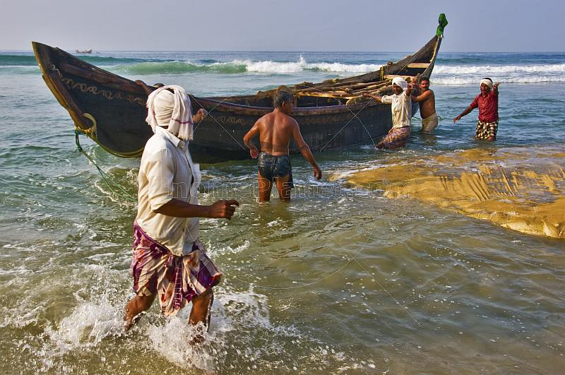 Fishermen bring their boat in through the surf.