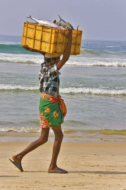 Man on the beach carrying a box of fish on his head.
