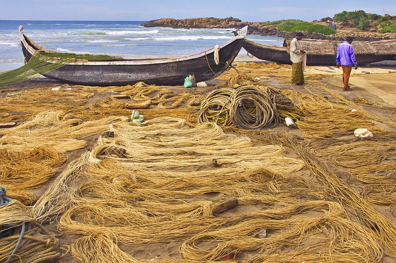 Fishermen dry their nets next to their boats on the beach.