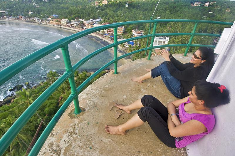 Two young Indian women enjoy the view of Kovalam Beach from the top of the Vizhinjam Lighthouse tower.