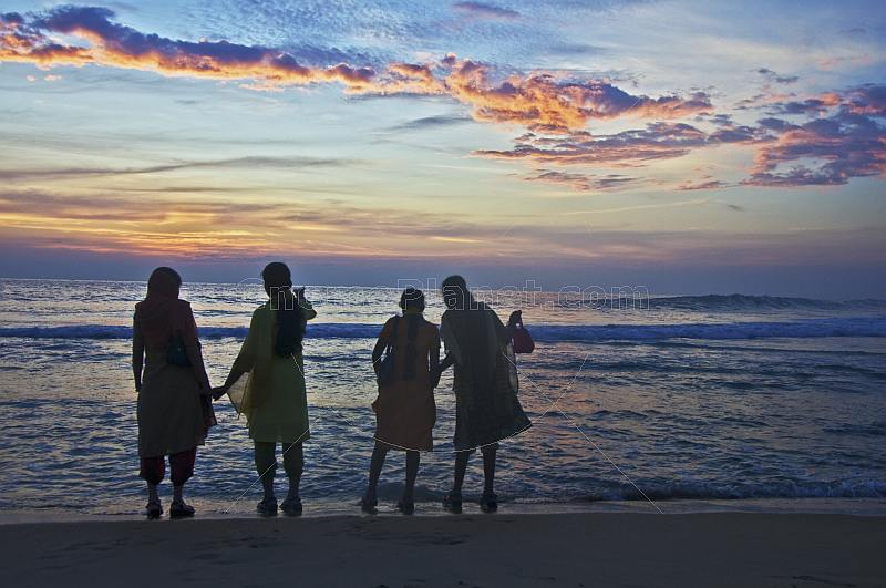 Four young Indian women watch the sunset.