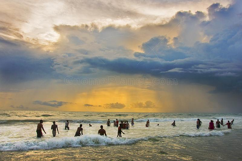 Indian bathers play in the surf during a cloudy sunset.