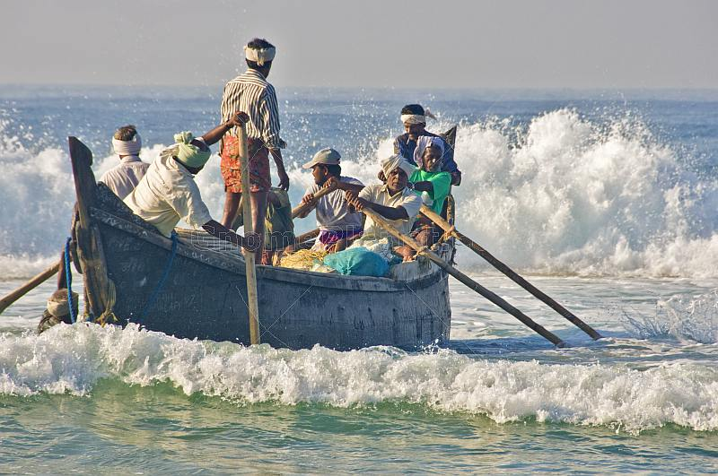 Fishermen battle the waves to launch their boat at Kovalam Beach.