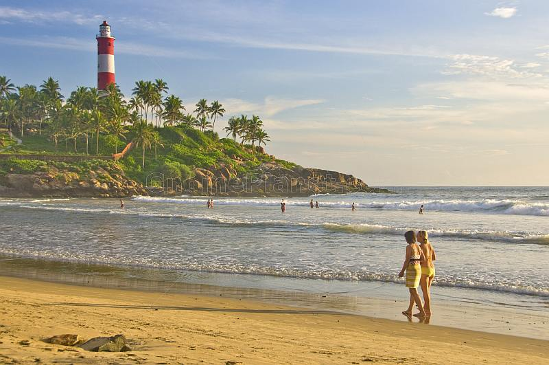 Two young Western women tourists walk along Lighthouse Beach.