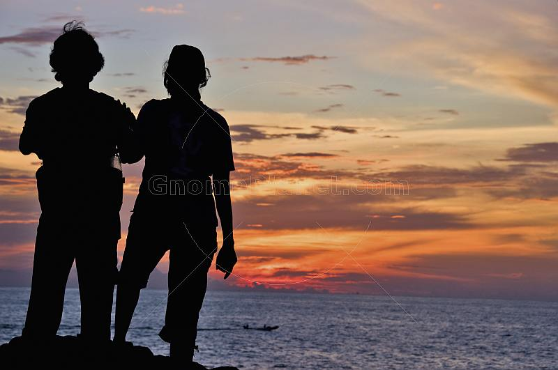Young Indian couple watch the sunset from rocks above Hawa Beach.