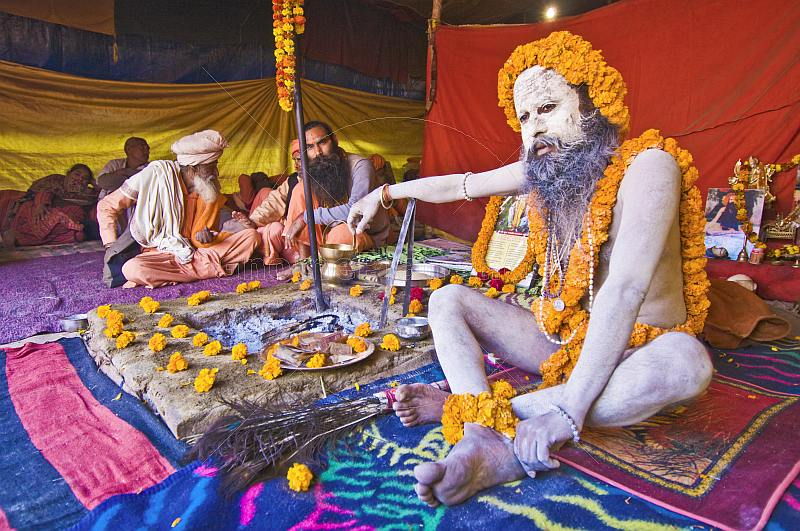 Juna Akhara Naga wearing marigold garlands squats next to sacred fire at Kumbh Mela.
